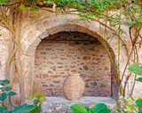 Greece, arch and ceramic jar in old stone house in Crete island