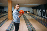 Male bowler standing on lane and poses with ball