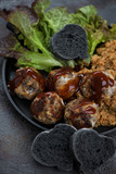Close-up of truffles made of mushrooms and cheese with black sliced baguette and salad leaves, selective focus