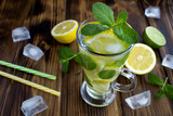 Cold  lemonade with lemon and mint  in the glass on the brown wooden background.Closeup.