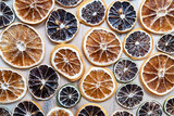 Dried citrus fruits (lemon, lime and orange) for decorating lie on a wooden textured table. Wallpaper. Top view.