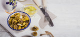 Grilled olives with garlic, olive oil and spices on white rustic table
