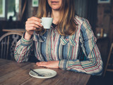 Young woman drinking espresso in a cafe