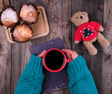 women's hands in a green knitted sweater holding a red ceramic mug with black coffee