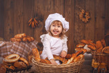 Happy baby chef in wicker basket laughing playing chef in bakery, lots of bread baking. rustic style