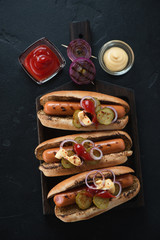 Three hot-dogs on a black wooden serving tray, flatlay over black stone background, studio shot