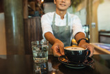 Portrait of smiling barista with coffee cup in front of customers at coffee shop. Portrait of happy young male coffee shop owner standing with barista working behind the counter bar.