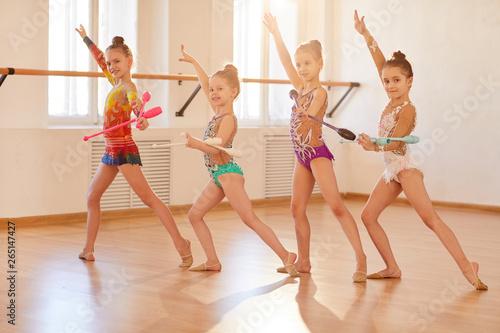 Team of little girls practicing rhythmic gymnastics with clubs