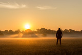 Silhouette of man in field at sunrise